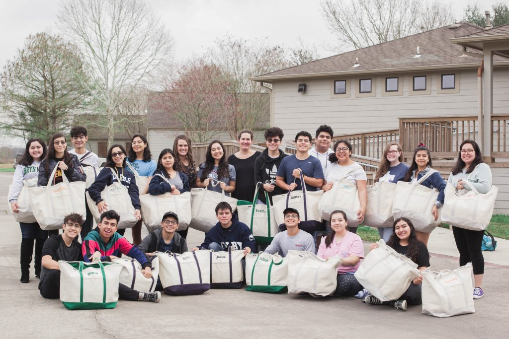 Chinquapin's Class of 2019 - 22 seniors all smiling for the camera, showing their appreciation for the college ready kits donated by Michelle and Mike Heinz and Stacy Brod.